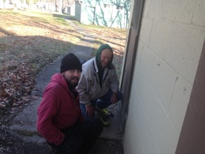 Nick and Jack are repairing the screen door on one of the cabins.